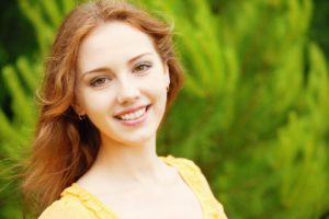Woman smiling against a green nature background