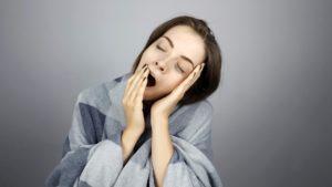 woman yawning against a grey background